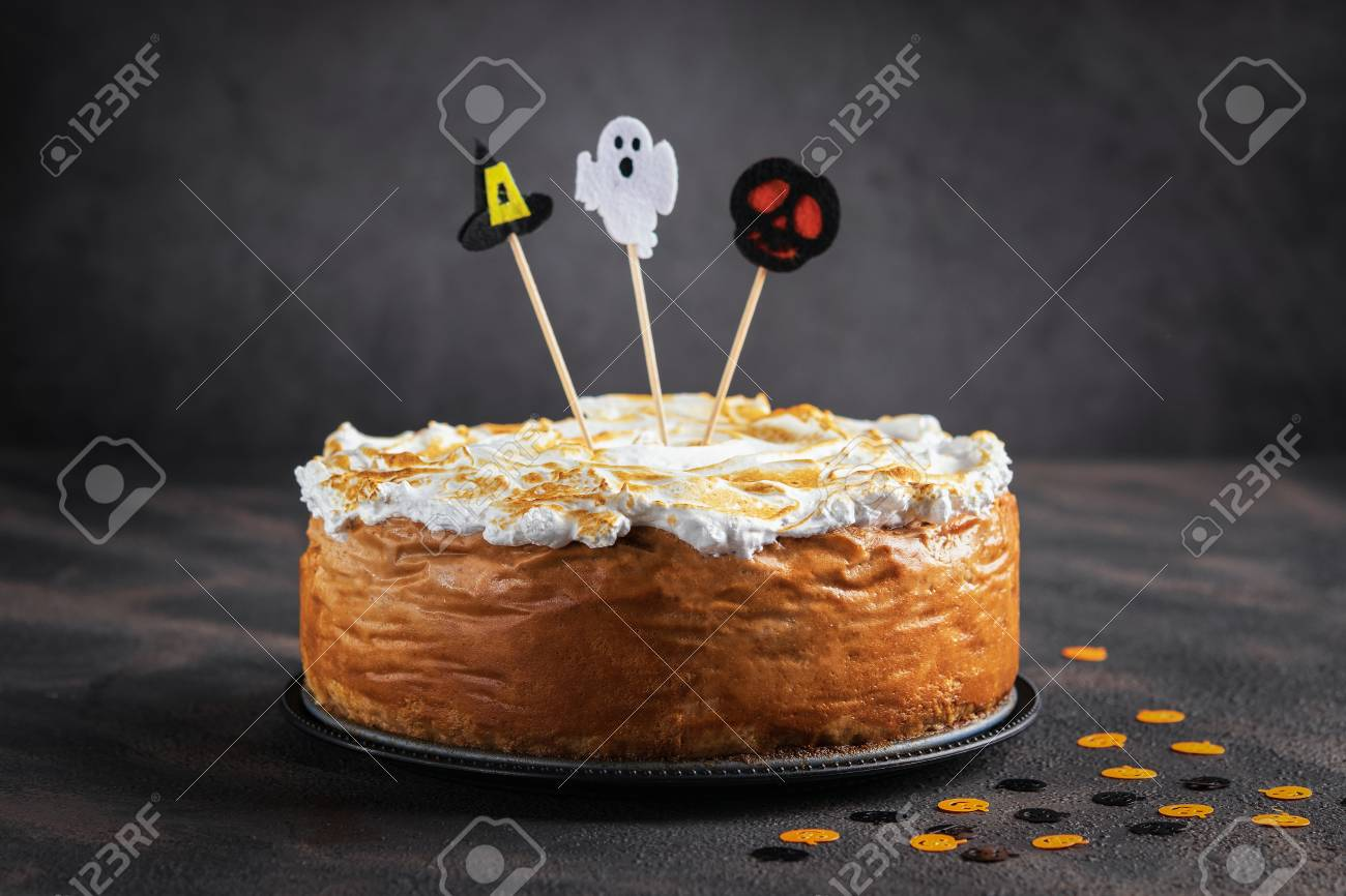 Halloween Pumpkin Cheesecake with Marshmallow Meringue Topping decorated with Halloween toppers. Dessert for Halloween and Thanksgiving. Space for text. Horizontal. Selective focus. - 110164670