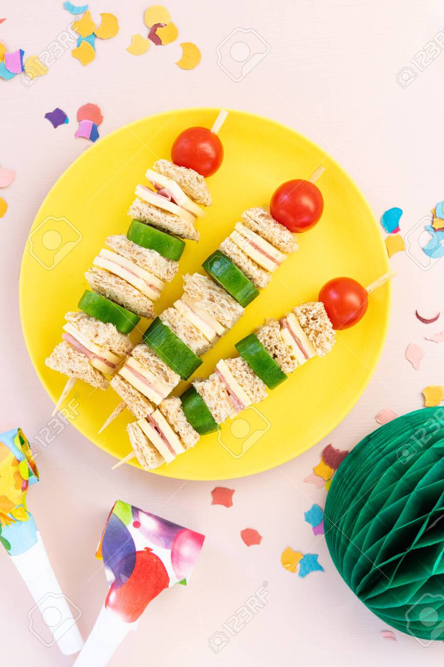 Mini Shaped Sandwich kabobs with cheese, ham, cherry tomato, cucumber and wholemeal bread over yellow plate on pink background with party decor, space for text. Kids party finger snacks food concept. - 145811060
