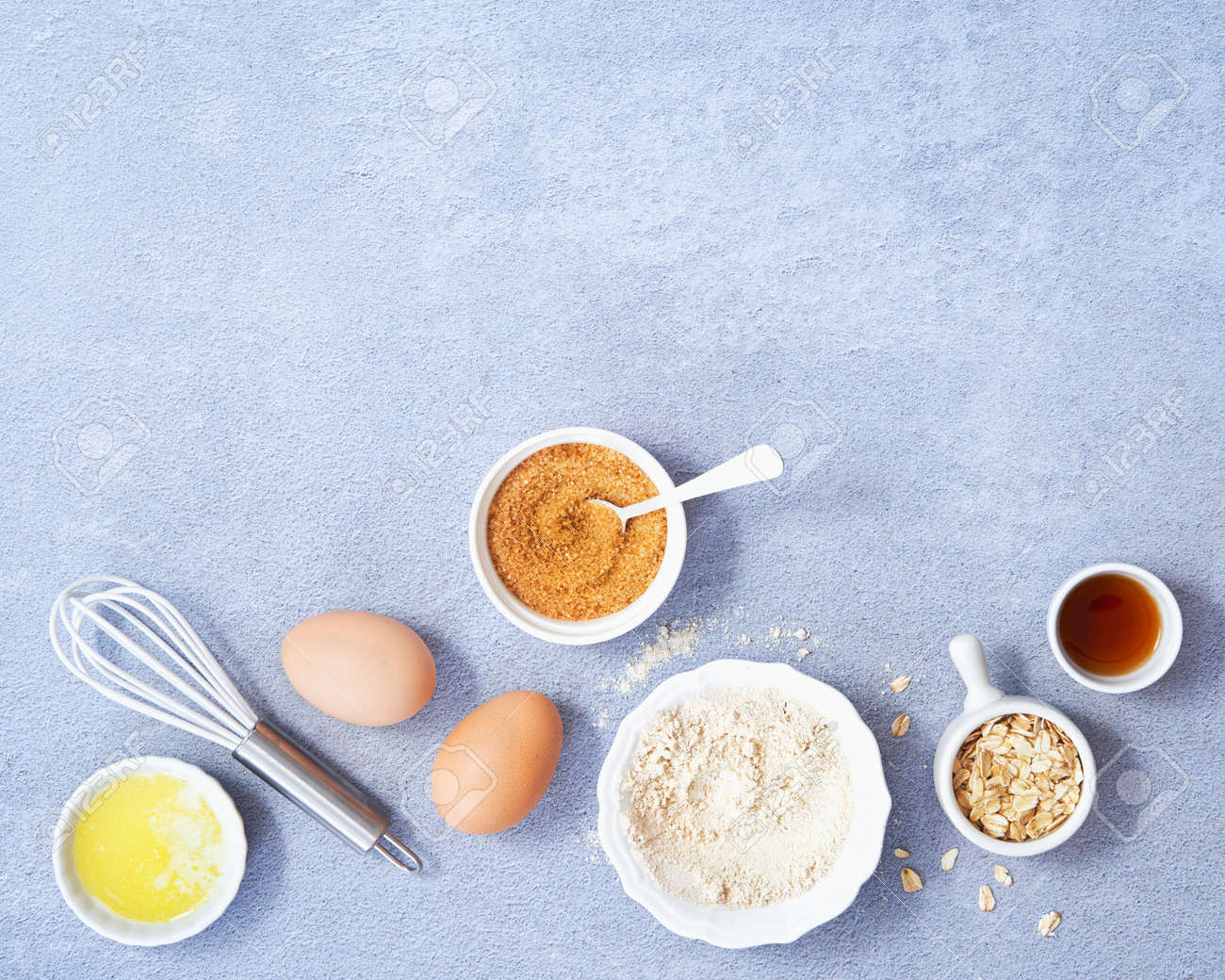 Ingredients for homemade oat pancake with whole grain oat, coconut sugar, vanilla syrup, organic eggs on light blue background. Healthy food recipe photography. Top view. Copy Space for text. - 171867015