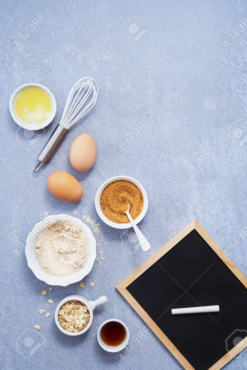 Ingredients for homemade oat pancake with whole grain oat, coconut sugar, vanilla syrup, organic eggs next to black chalkboard in a pen, light background. Healthy food recipe. Top view. Space text. - 172881241