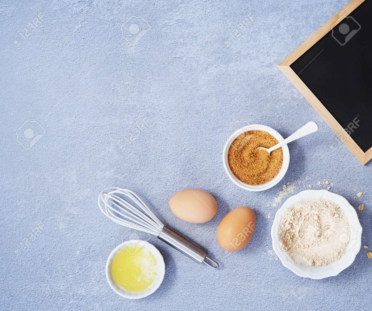 Ingredients for homemade oat pancake with whole grain oat, coconut sugar, vanilla syrup, organic eggs next to black chalkboard on light blue background. Healthy food recipe. Top view. Space for text. - 171806647