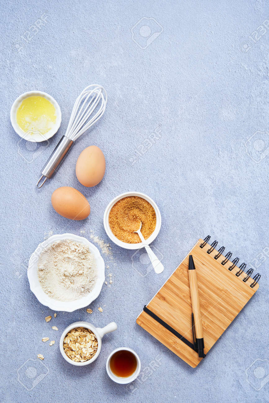 Ingredients for homemade oat pancake, whole grain oat, coconut sugar, vanilla syrup, organic eggs a notebook in a pen on light blue background. Healthy food recipe photography. Copy space. Top view. - 171867022
