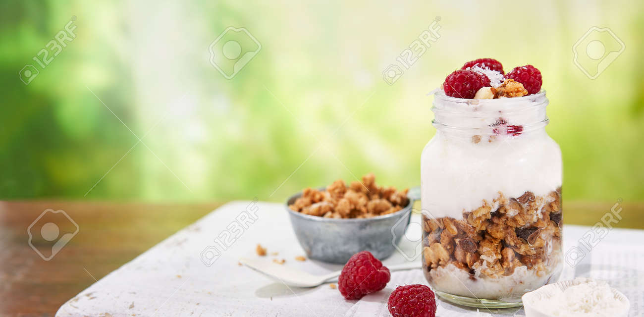 Granola with greek yogurt parfait fresh raspberries, coconut in a glass on wooden table outdoors. Healthy and tasty summer breakfast. Food Banner background with copy space. - 172634947