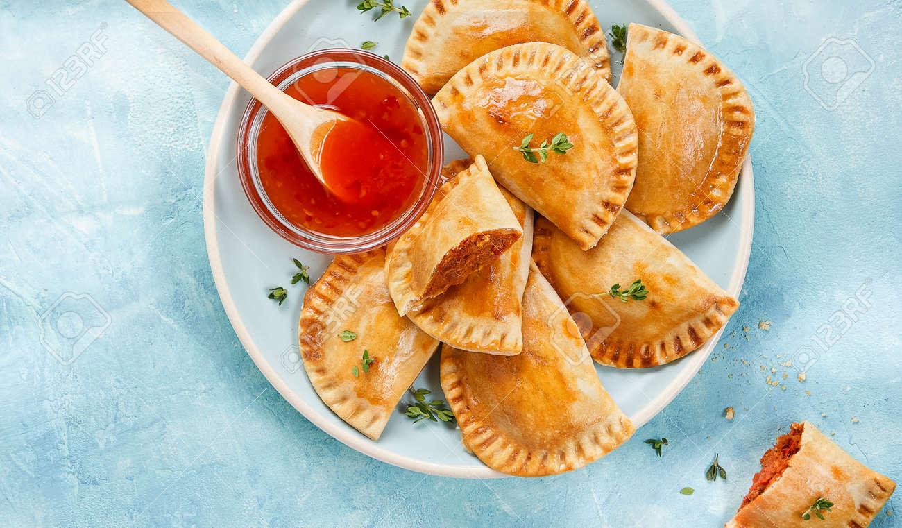 Banner Empanadillas, small filling tuna pies, tomato sauce, bell pepper, boiled egg. Close up. Spanish Mediterranean food. - 173009975