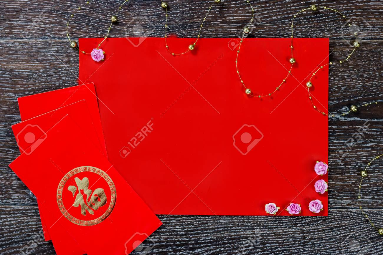 Chinese New Year Red Envelope With Wish On Dark Wood And Background Pink Flowers