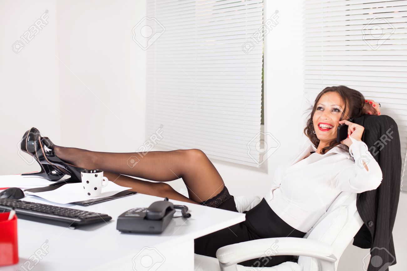 hot office pic. Hot Business Woman Sitting In The Office With Legs On Table And Talking Mobile Pic G
