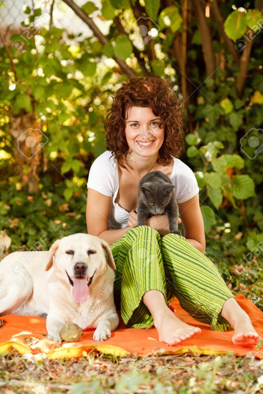 Stock Photo - Young beautiful woman relaxing in nature with pets