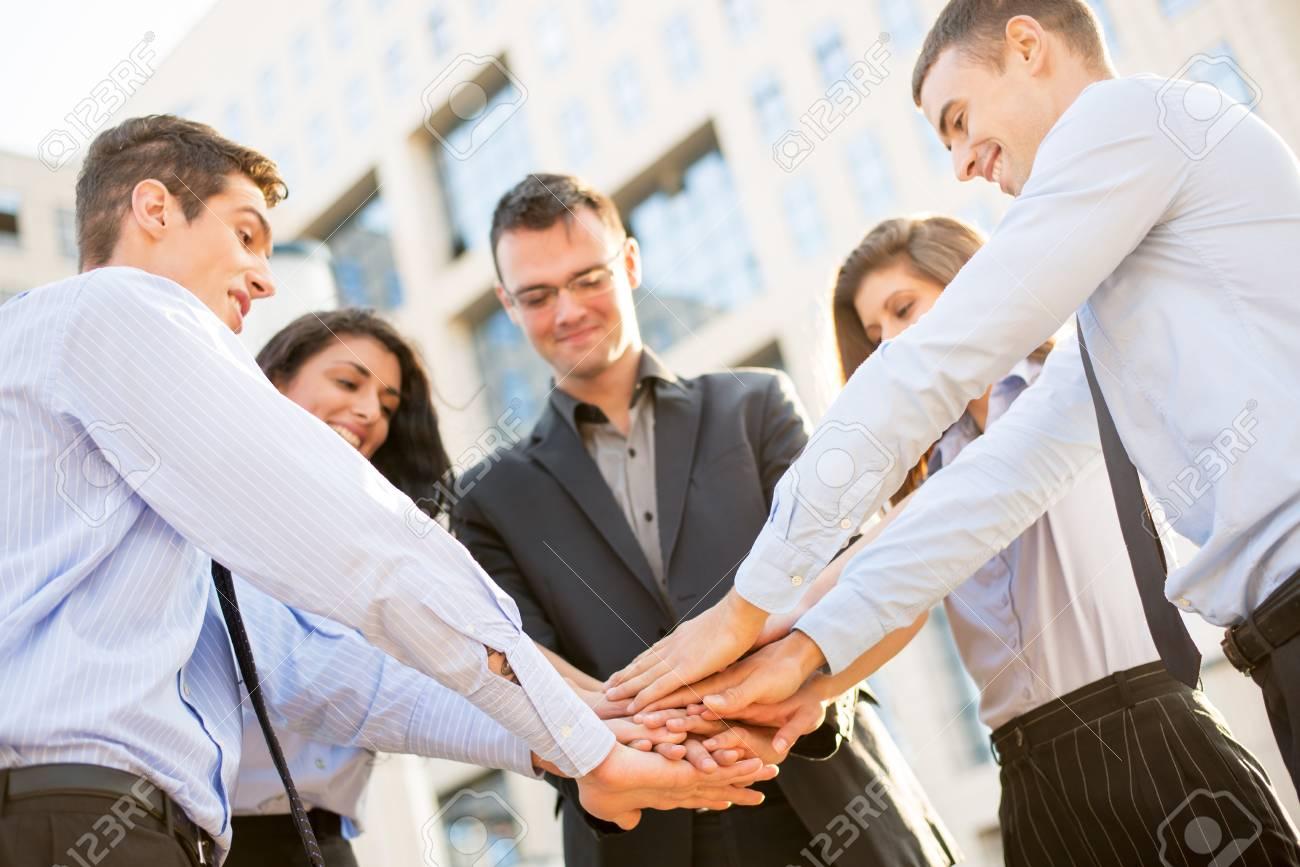 Un Pequeño Grupo De Jóvenes Empresarios De Pie En Frente De La Empresa Con Las Manos Juntas De Motivación Para Nuevas Victorias De Negocios