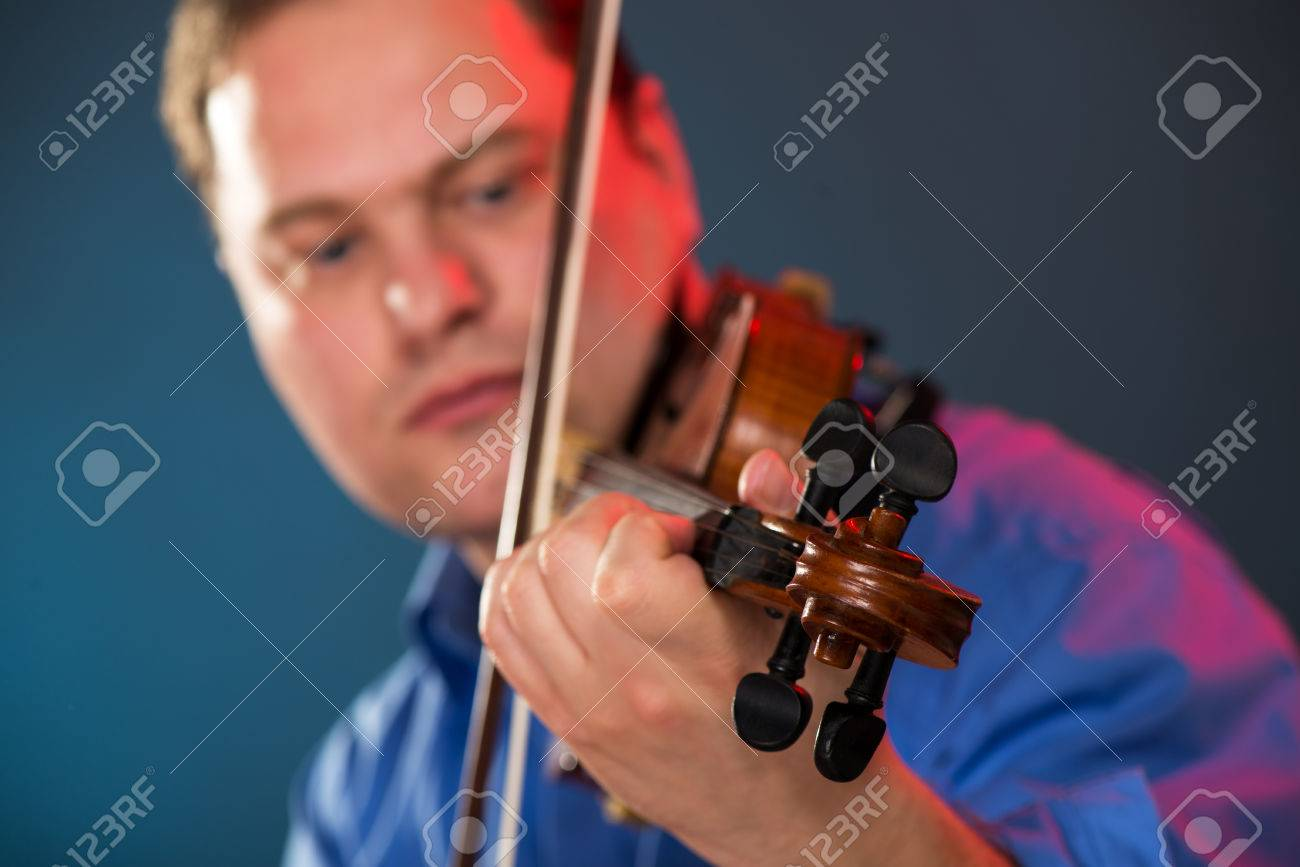 Close-up of violin in the hands of the violin virtuoso with a face out of focus. - 35762280
