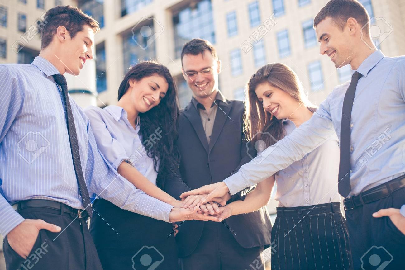 Grupo De Jóvenes Empresarios De Pie En Frente De La Empresa Con Las Manos Juntas De Motivación Para Nuevas Victorias De Negocio