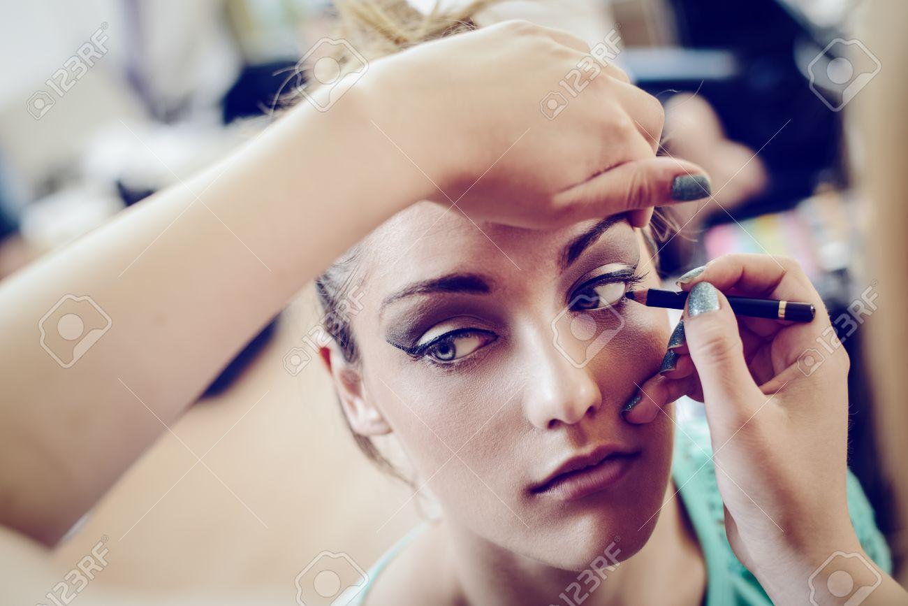 Une jolie femme ayant maquillage appliqué par une maquilleuse
