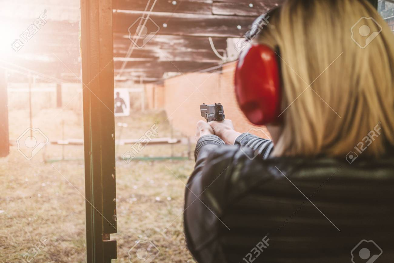 a20dc35690b48 Stock Photo - Woman firing with pistol on target at the shooting range.  Rear view.