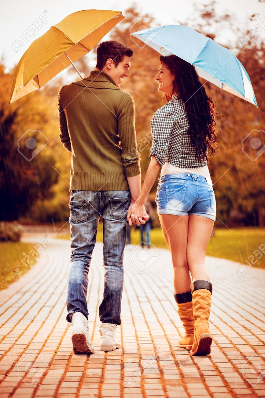 Beautiful Lovely Couple With Umbrellas Enjoying While Walking