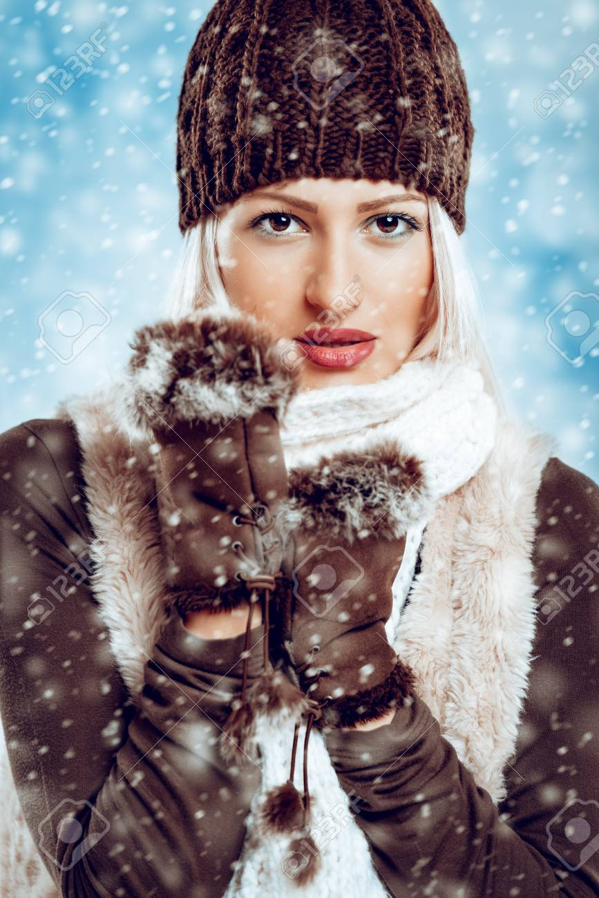 6be2dcb661d7 Beautiful young girl in winter clothes with a wool cap and fur gloves