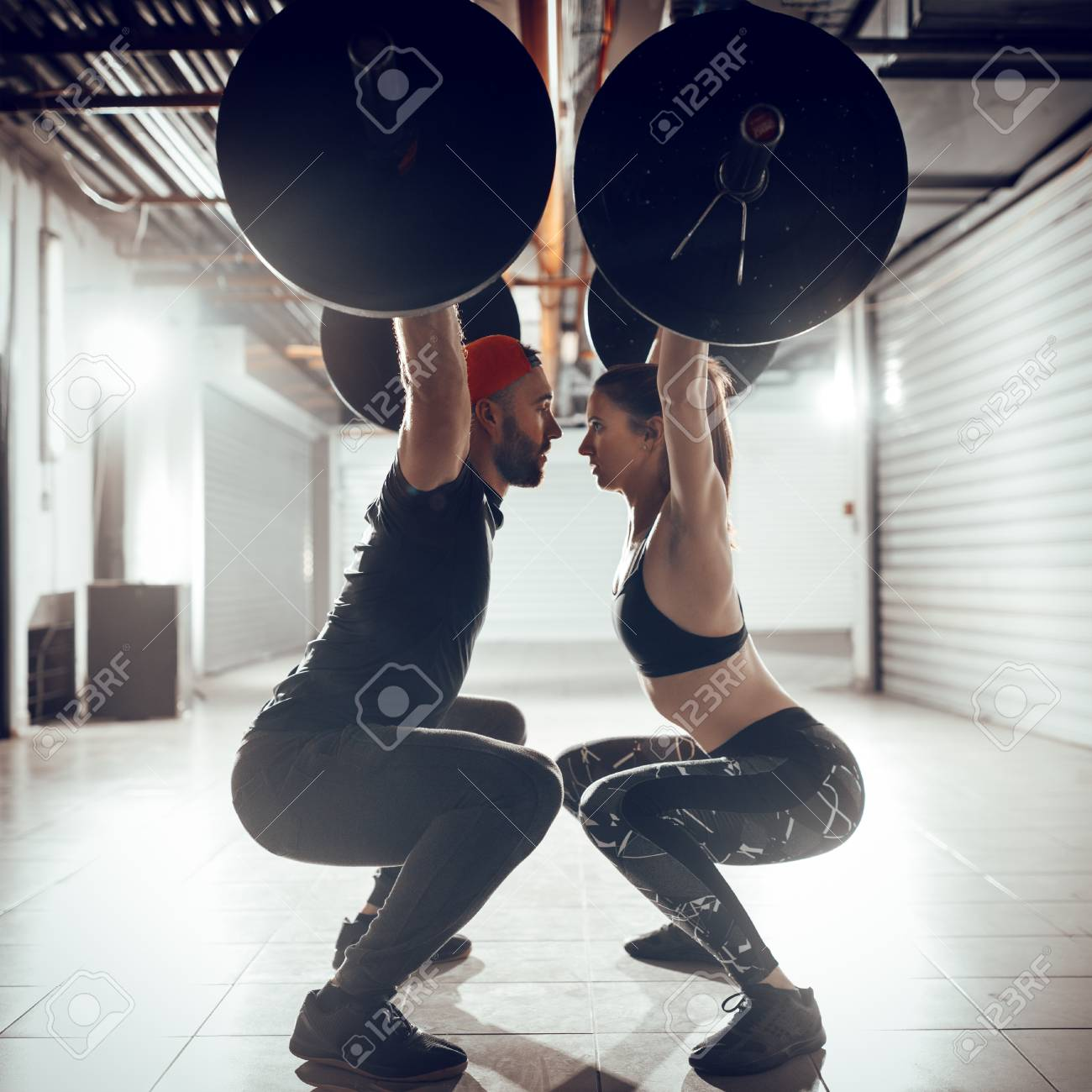 Young muscular couple doing overhead squat exercise with barbell