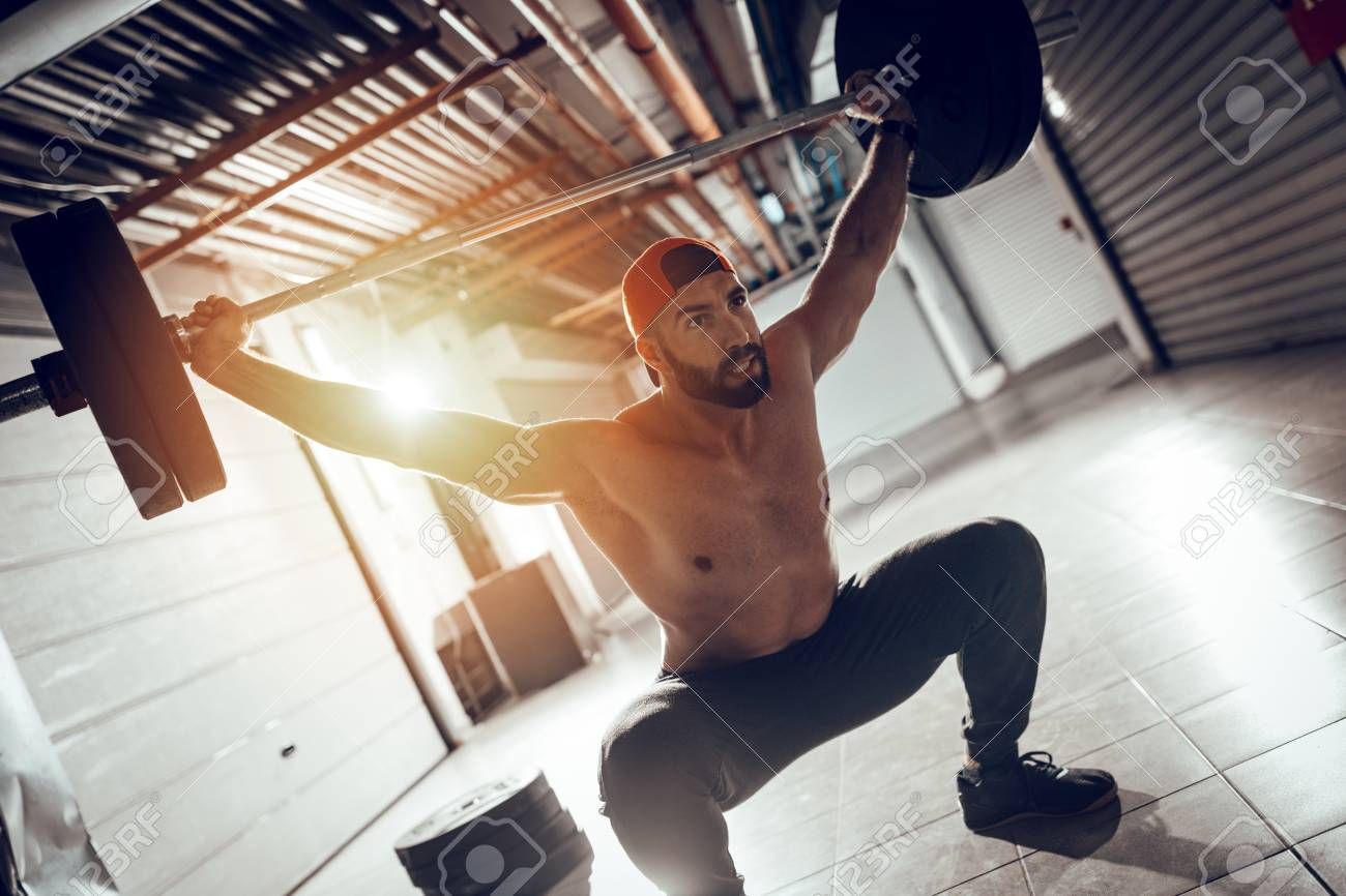 Young muscular man doing overhead squat exercise with barbell