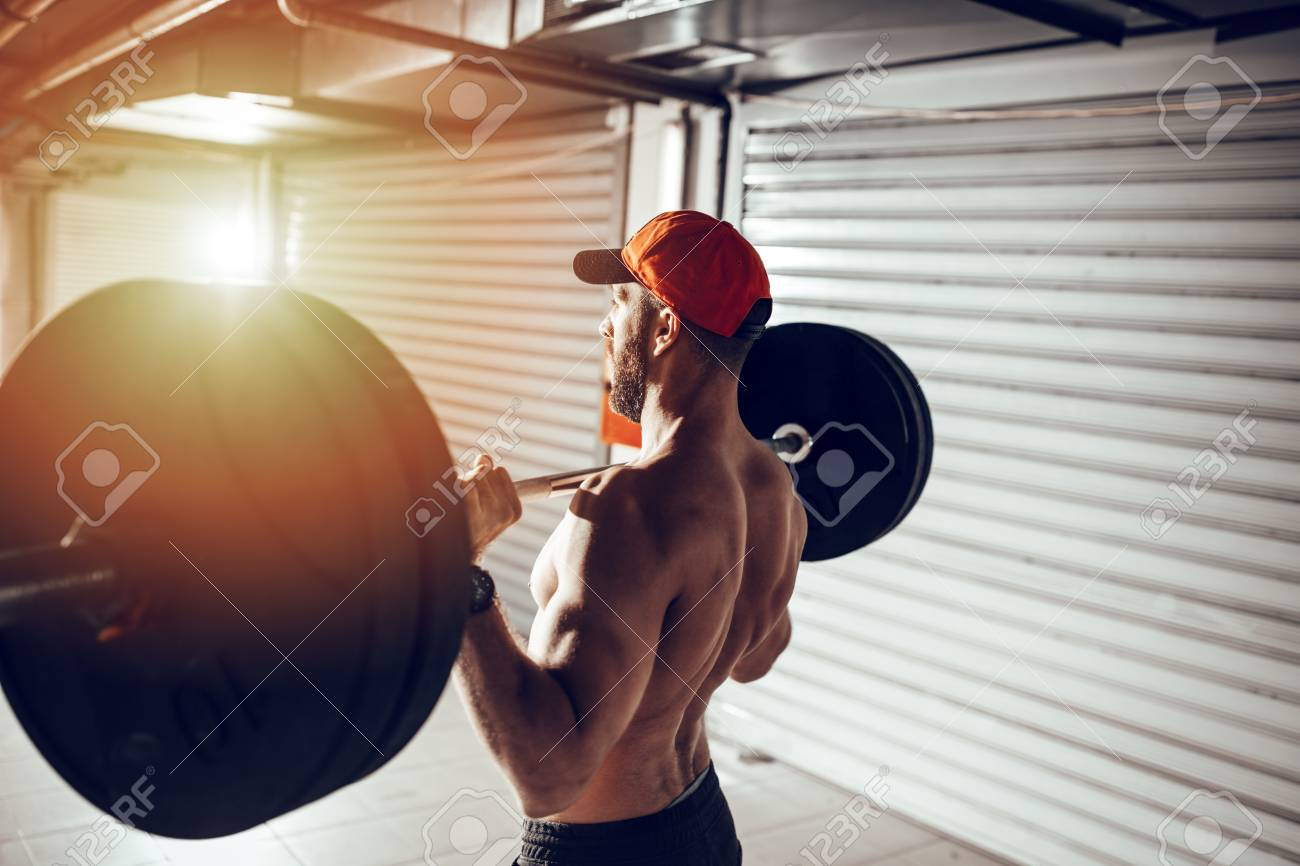 Young muscular man doing high pull exercise with barbell on cross