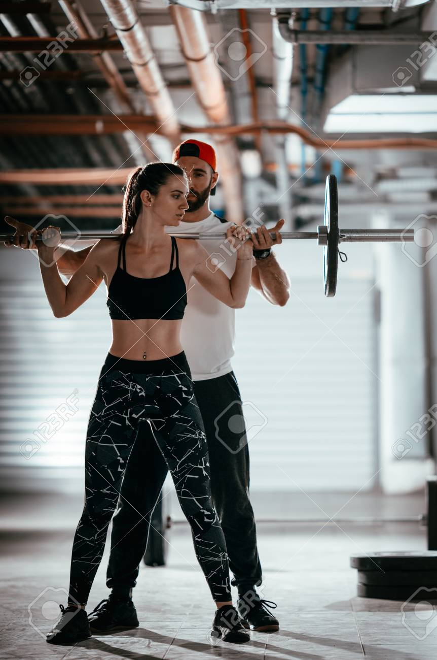 Young muscular woman doing cross workout with a personal trainer