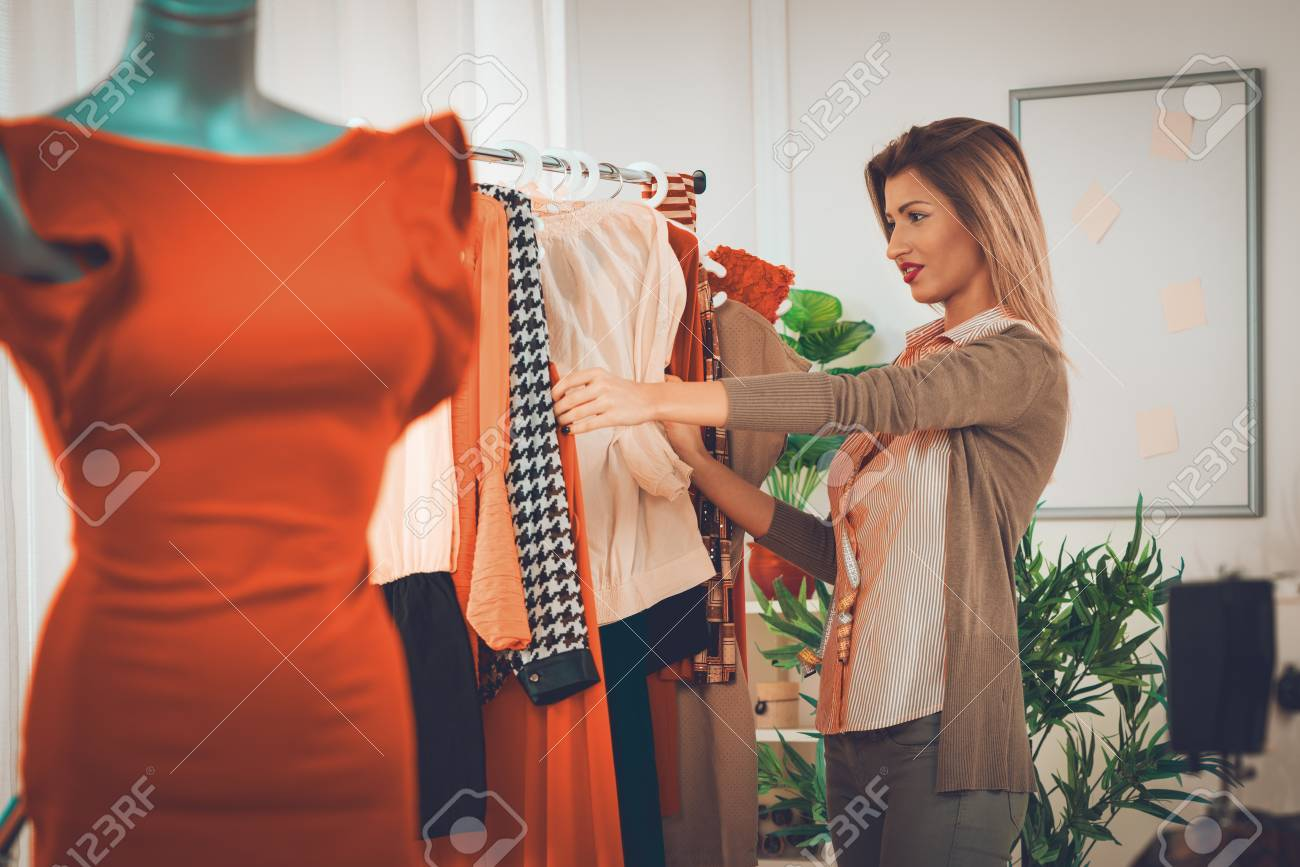 Beautiful young woman choosing clothing at the fashion designer office. In  the foreground you can 8a423668f