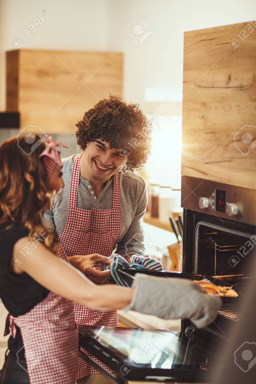 Young smiling happy couple put a pizza in the oven to bake, making fun. - 129198421
