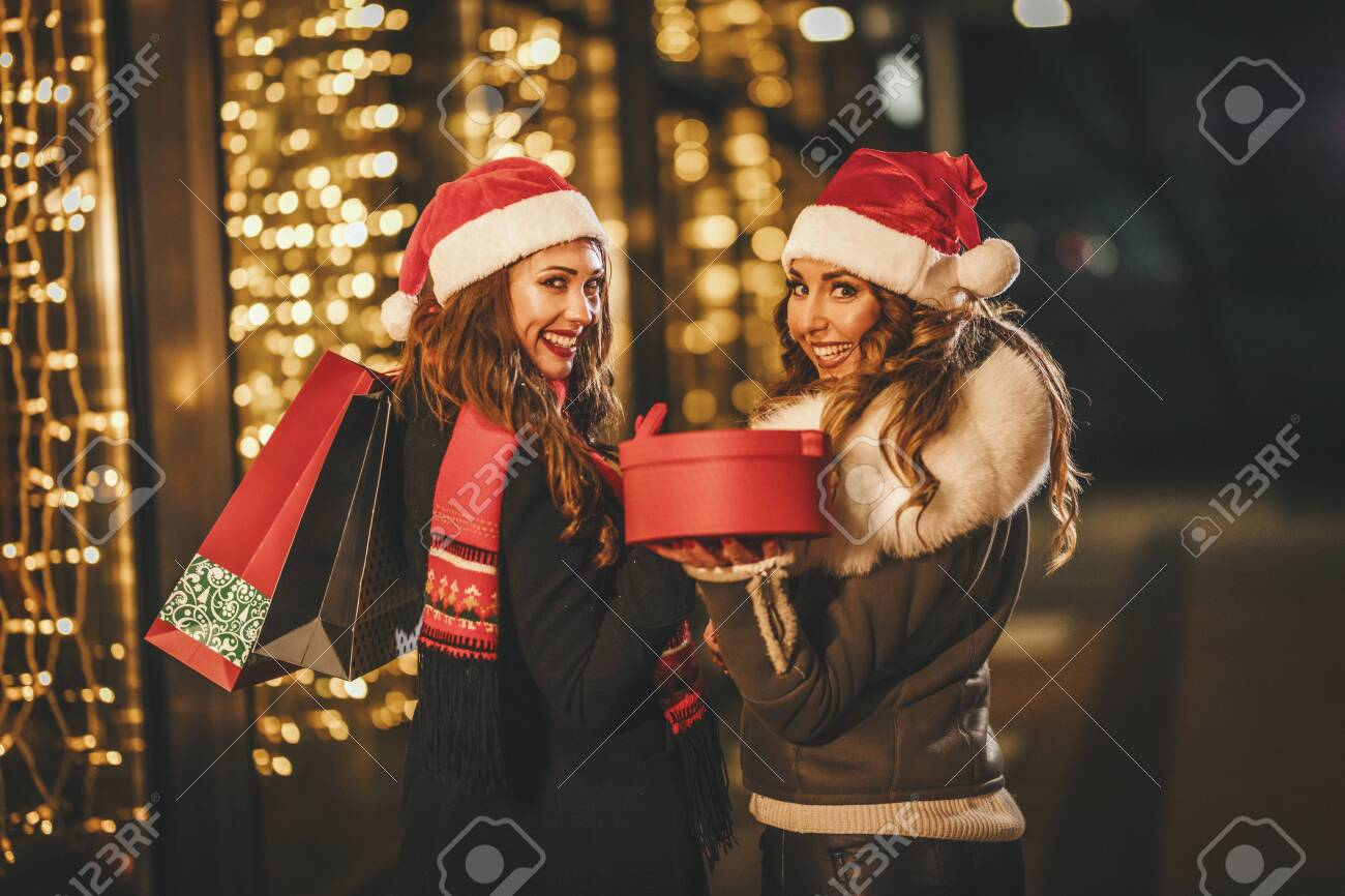 Two female friends enjoy the winter night and laughing with shopping bags and red box in their hands. - 154445079