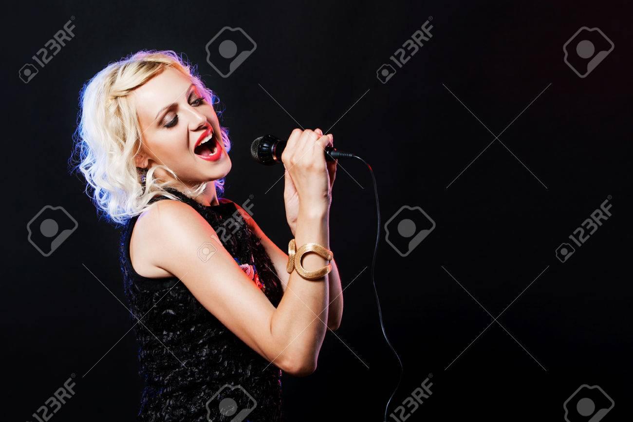 Schöne Frau mit Mikrofon singen Karaoke Singer Song auf schwarzem  Hintergrund