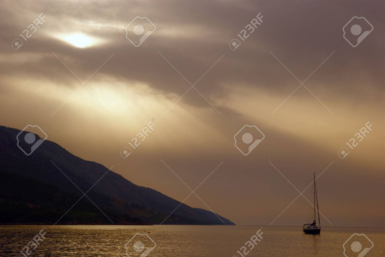 dramatically beautiful landscape with sea, ship and sun covered with clouds Stock Photo - 2914060