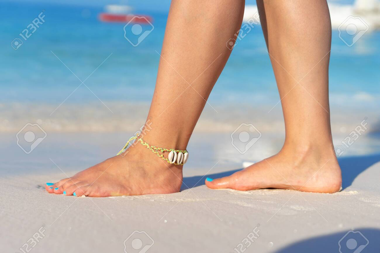 Girl standing barefoot on the sand beach female feel walking in summer vacation sunny day by the sea or ocean - 131415708