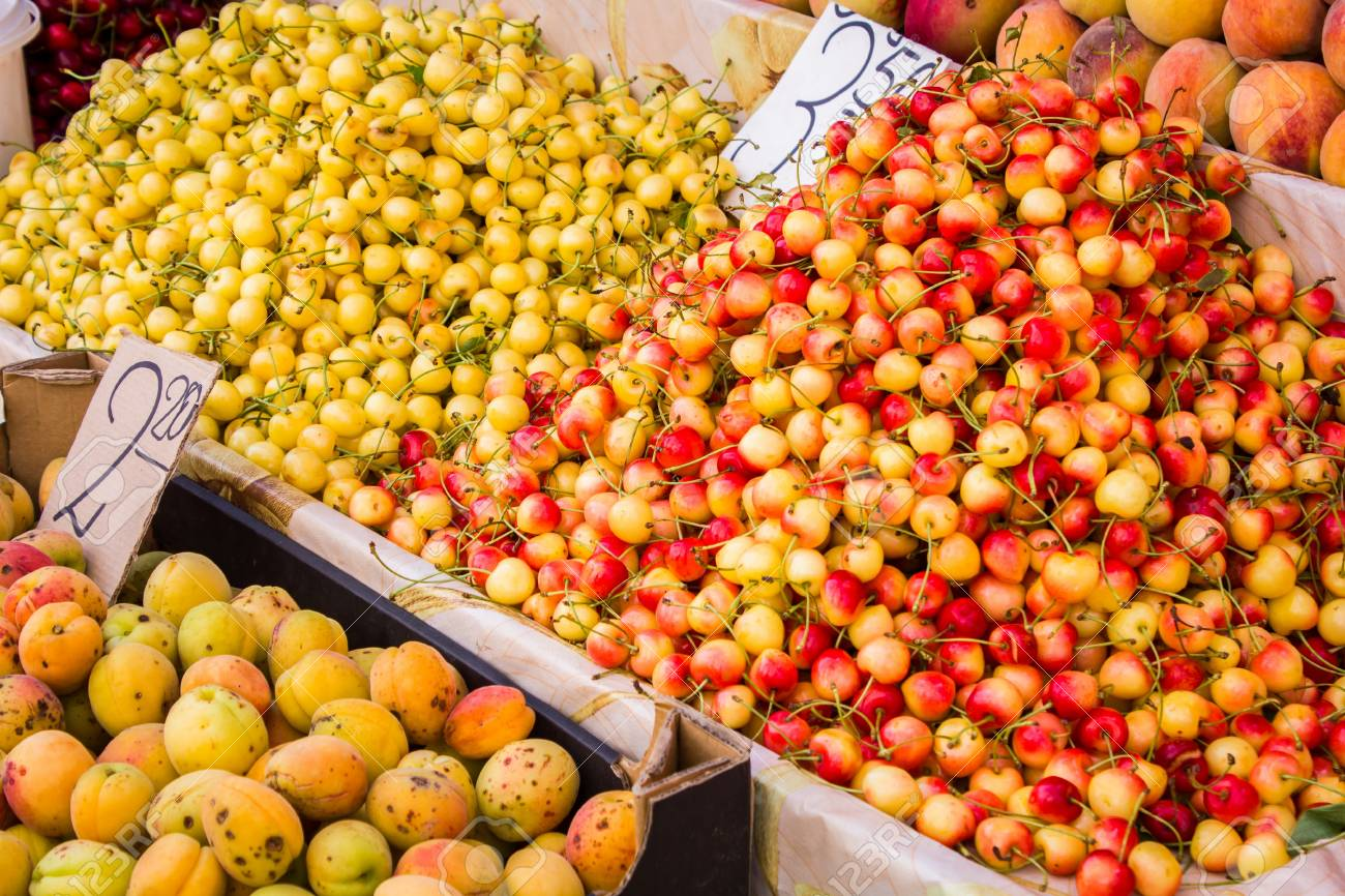 Big juicy ripe delicious sweet cherries next to other fruits are sold at the counter - 60870226