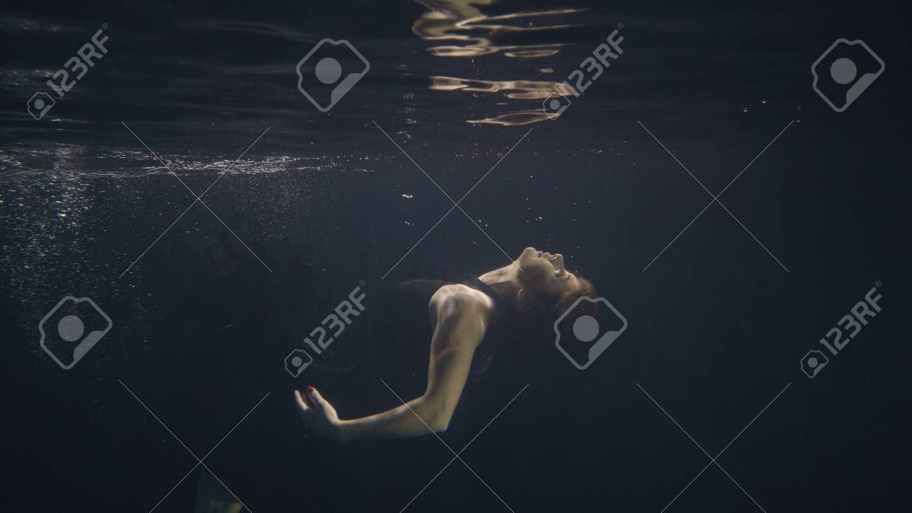603c45dab1 Stock Photo - Young woman in black dress swimming underwater in pool while  video shooting