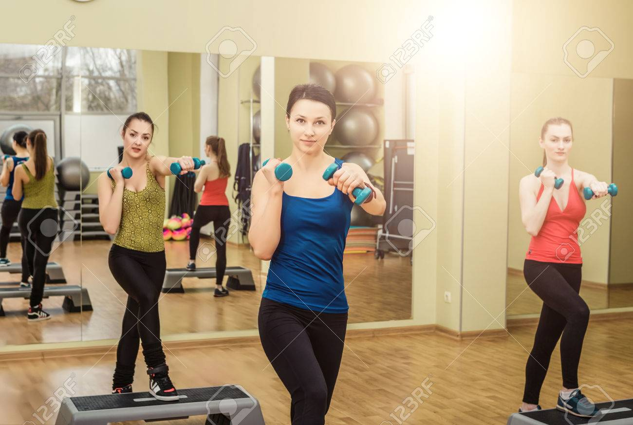 group of women making step aerobics in the fitness class stock photo