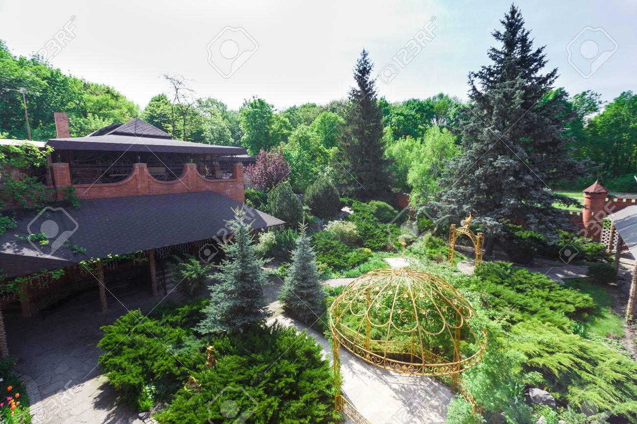Belle conception de paysage, chemin de jardin avec des carreaux de pierre,  des buissons à feuilles persistantes, sapins, épicéas bleus et arbustes à  ...