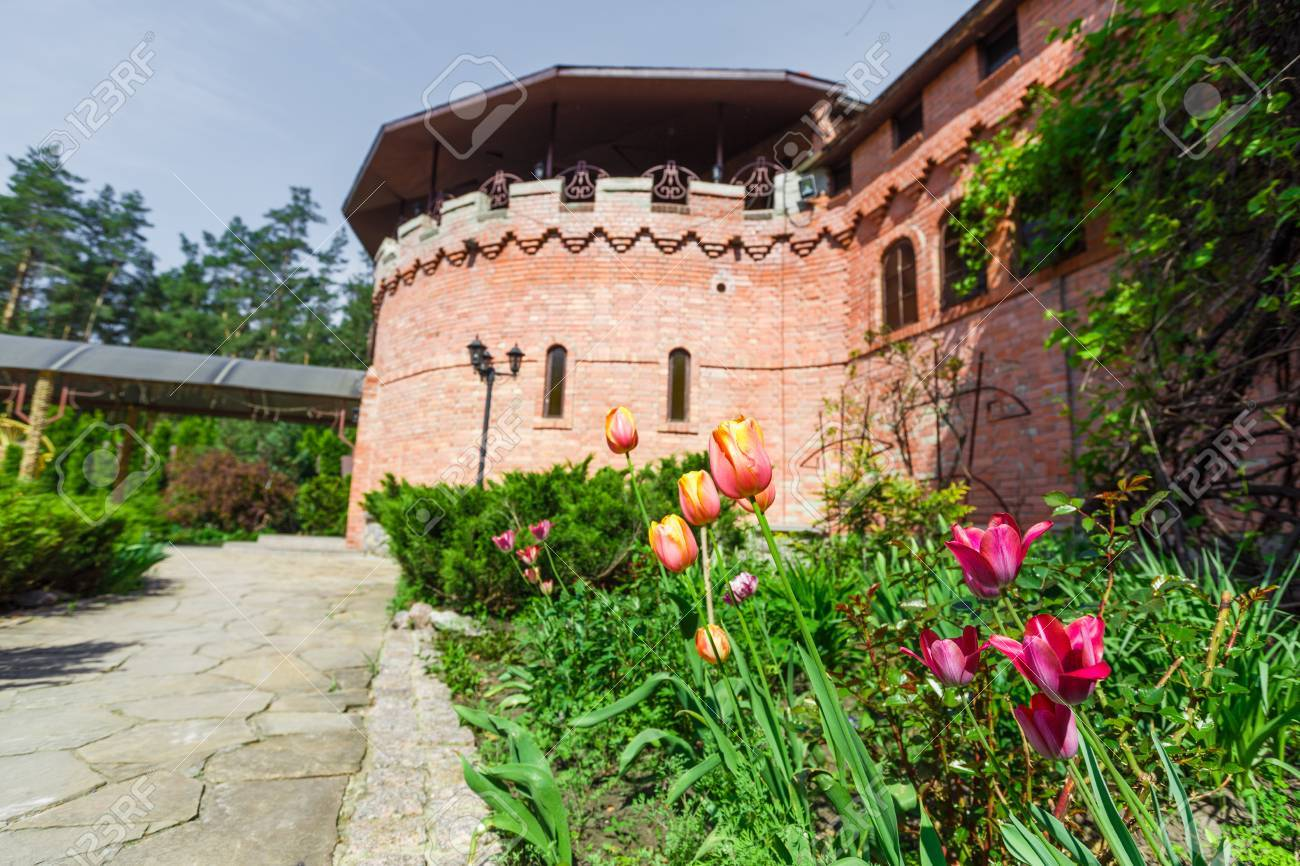 Tulipes rouges et roses dans le jardin près du château. L\'aménagement  paysager du jardin. aménagement paysager moderne. Parterre de fleurs et à  ...