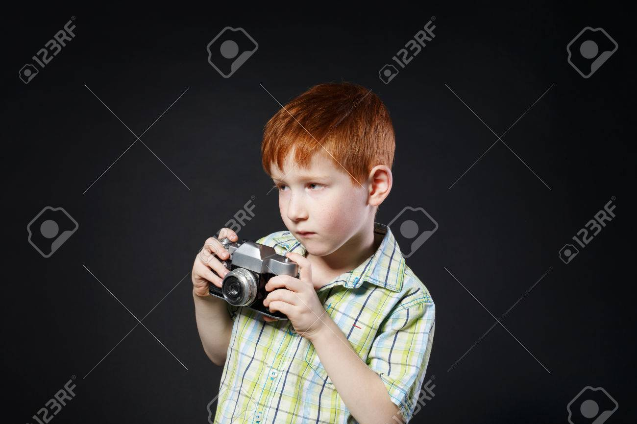 Little cute boy take photo with old vintage film camera at black  background. Small redhead