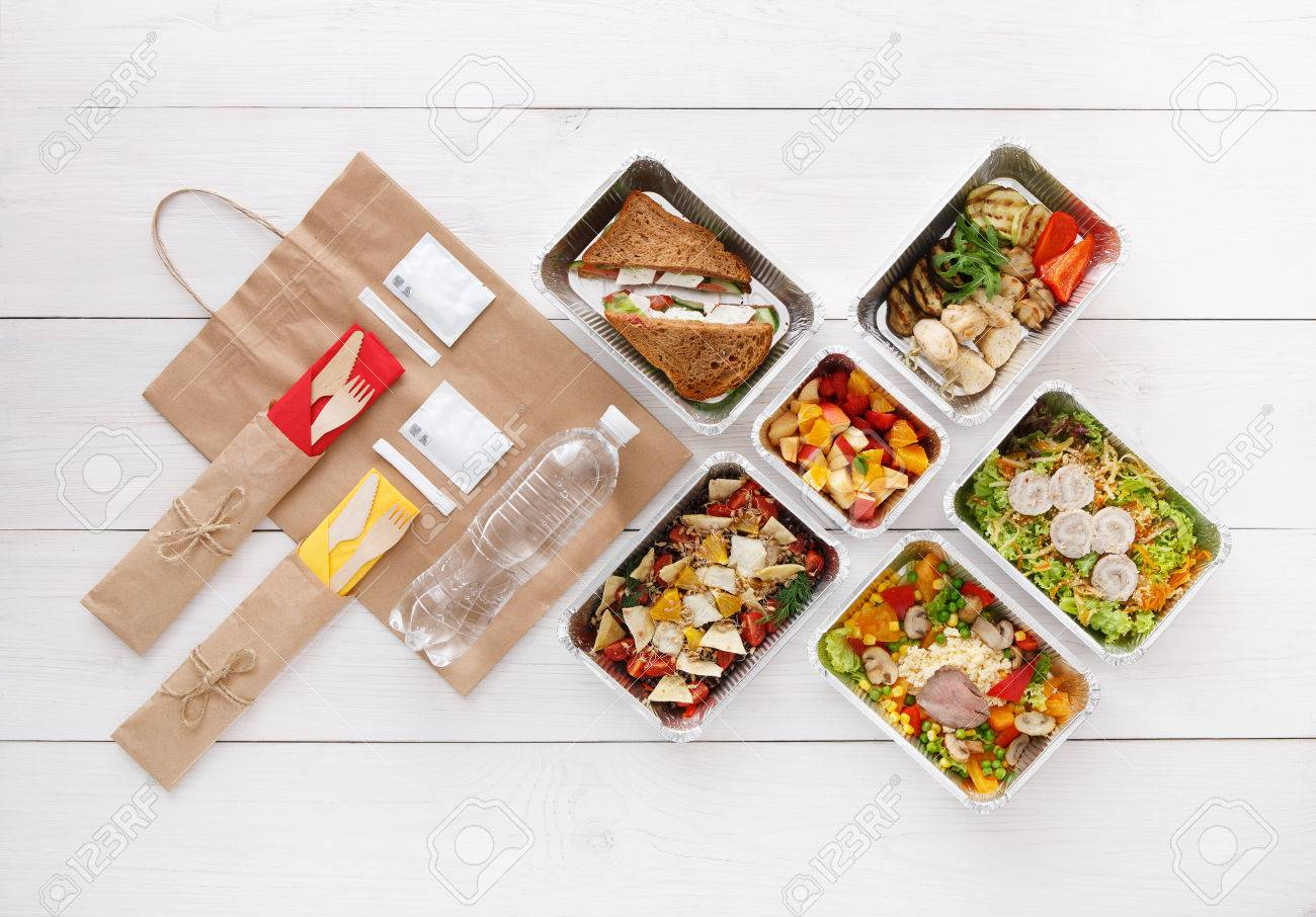 Healthy food delivery. Take away for diet. Fitness nutrition, vegetables, meat and fruits in foil boxes, cutlery, water and brown paper package. Top view, flat lay at white wood with copy space - 59486675