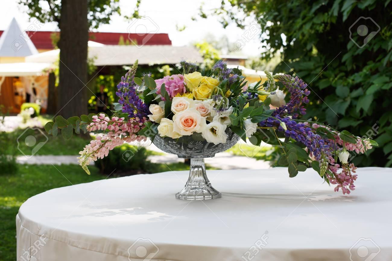 Décoration De Mariage Floristique Au Blanc Table Ronde, Bouquet De Fleurs  Colorées Et Roses Blanches Dans Un Vase En Verre