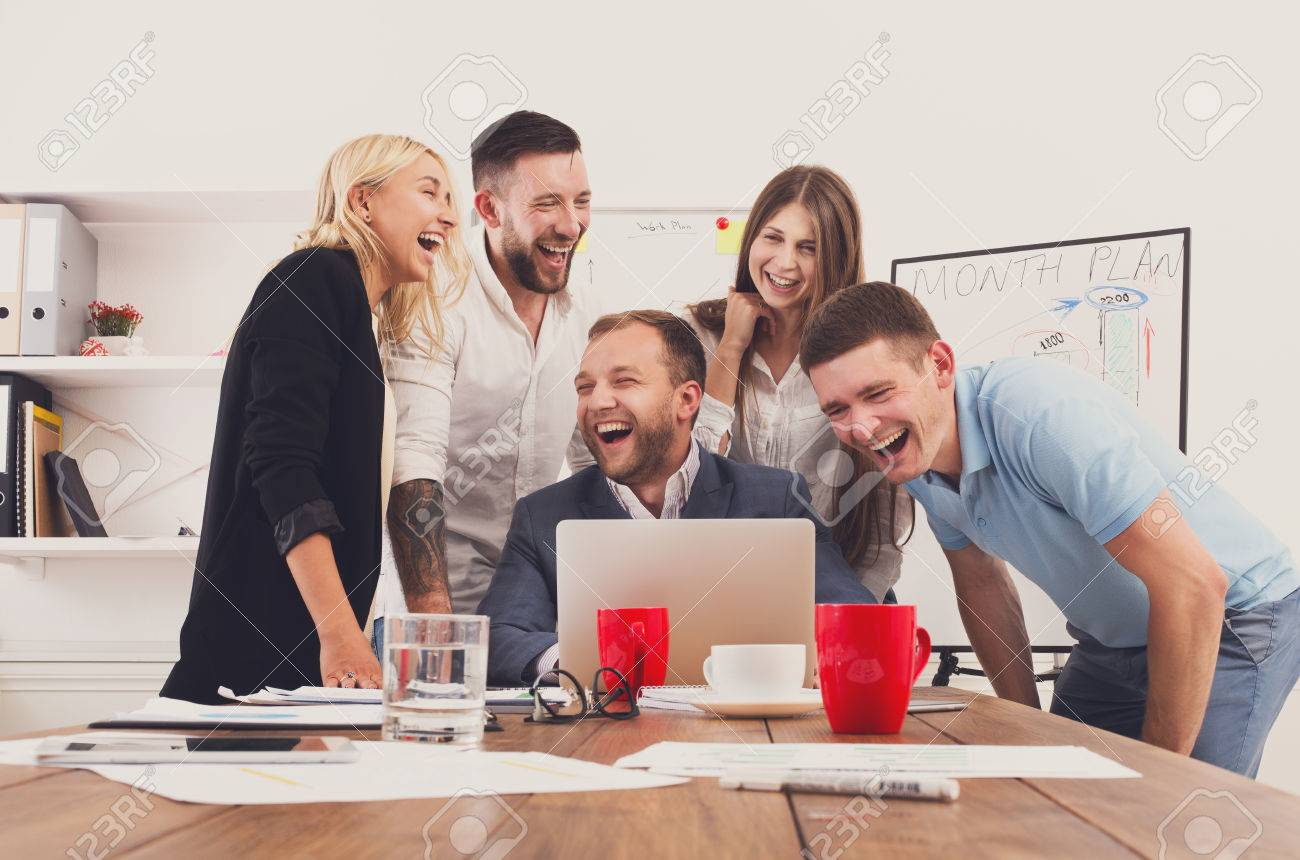Happy business people laugh near laptop in the office. Successful corporate team of female and male coworkers joke and have fun together at work - 61516986