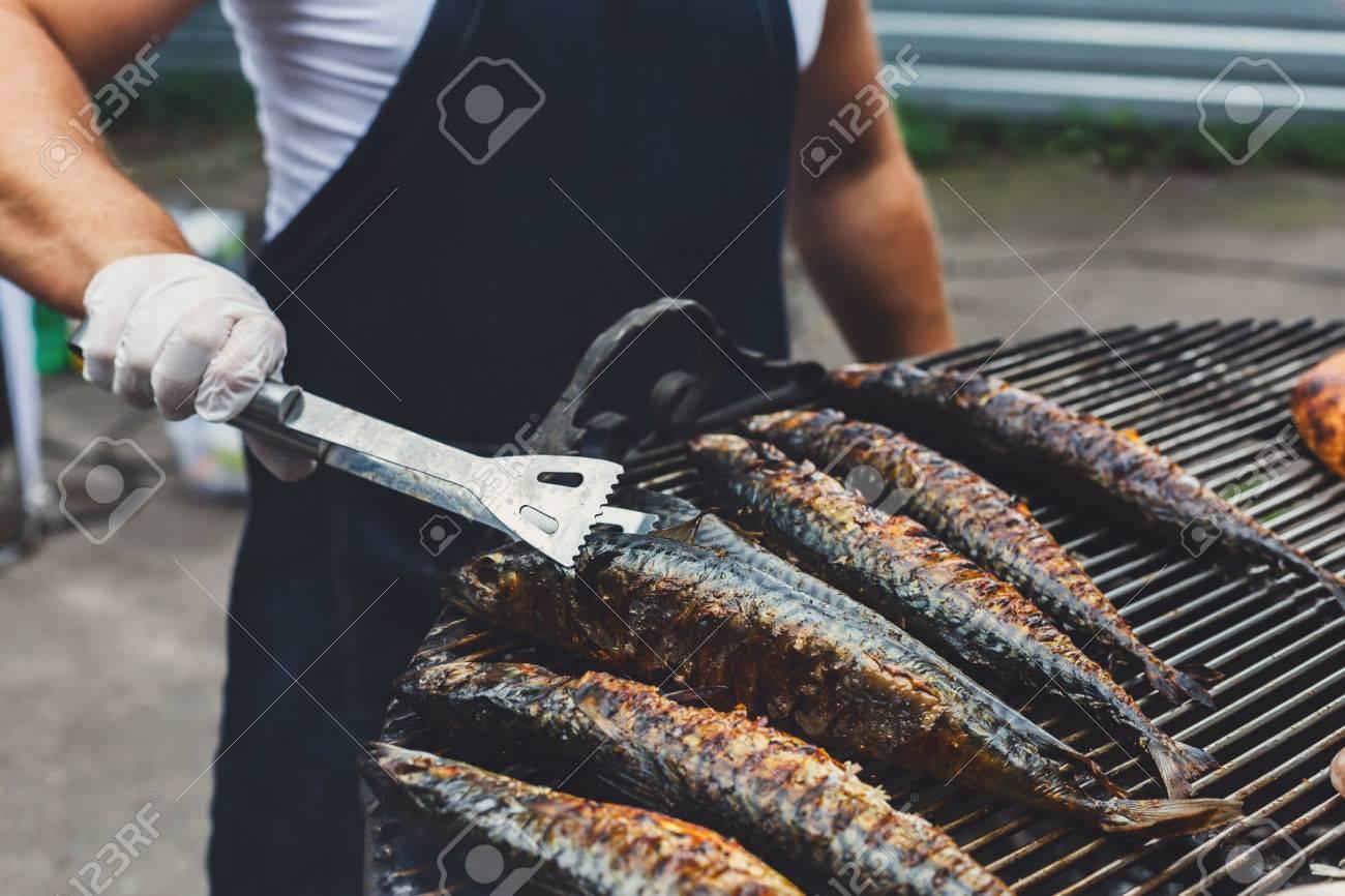 chef cookind am grillrost. viele makrele fisch gegrillt auf grill