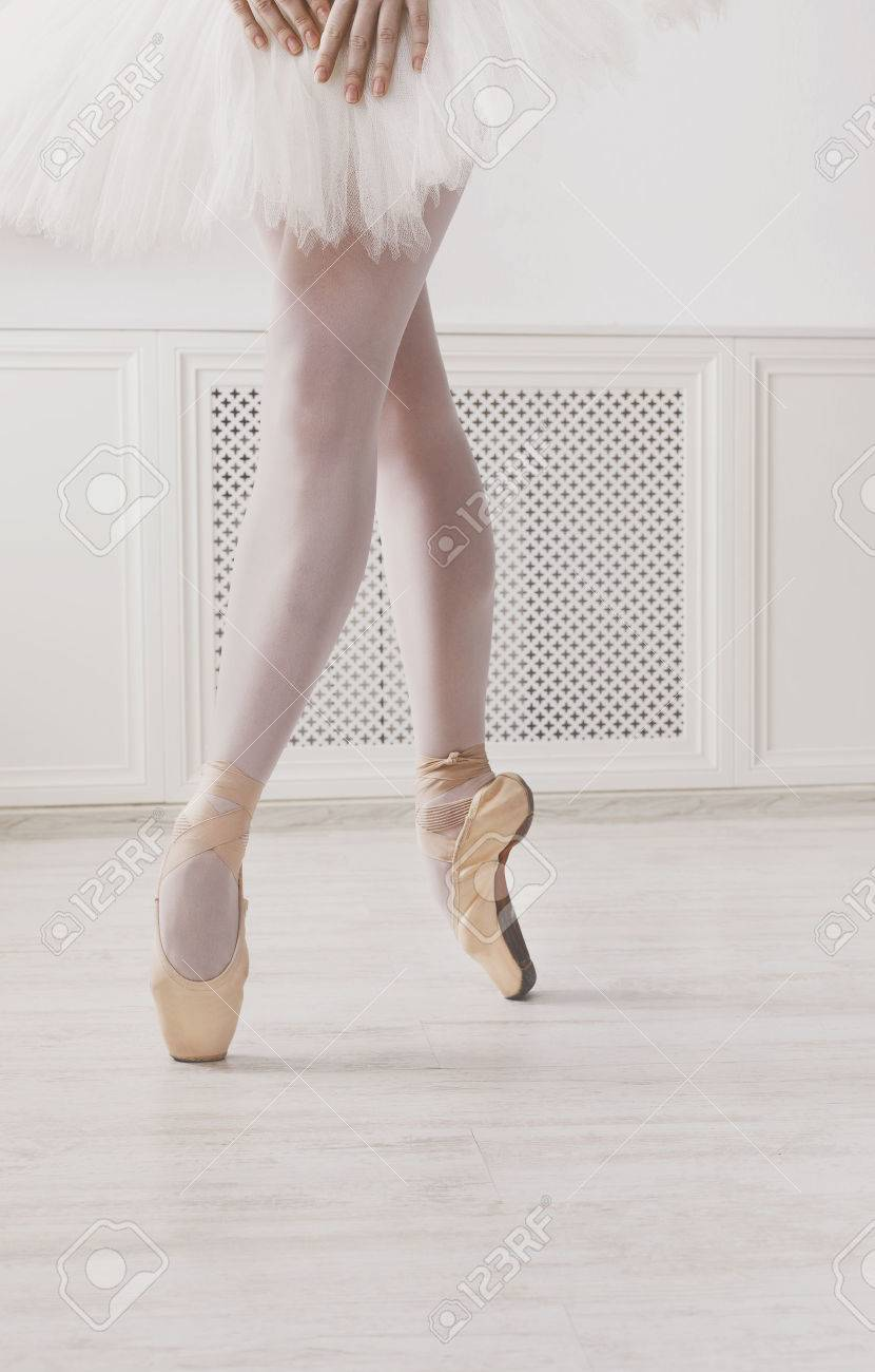 ed033f8f8775f Closeup legs of young ballerina in pointe shoes at white class room  background. Ballet practice