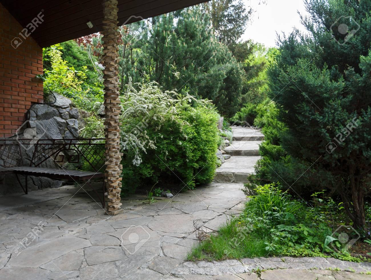 Beau Design Paysager Allee De Jardin Avec Escalier En Dalles De Pierre Arbustes A Feuillage Persistant Et Arbustes Au Soleil Banc Dans Un Beau