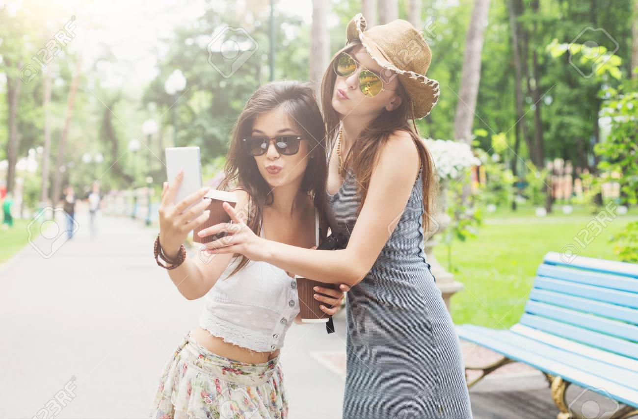 12b32160ea Stock Photo - Two girls friends outdoors take selfie with smartphone. Young  female tourists in boho chic fashion clothes