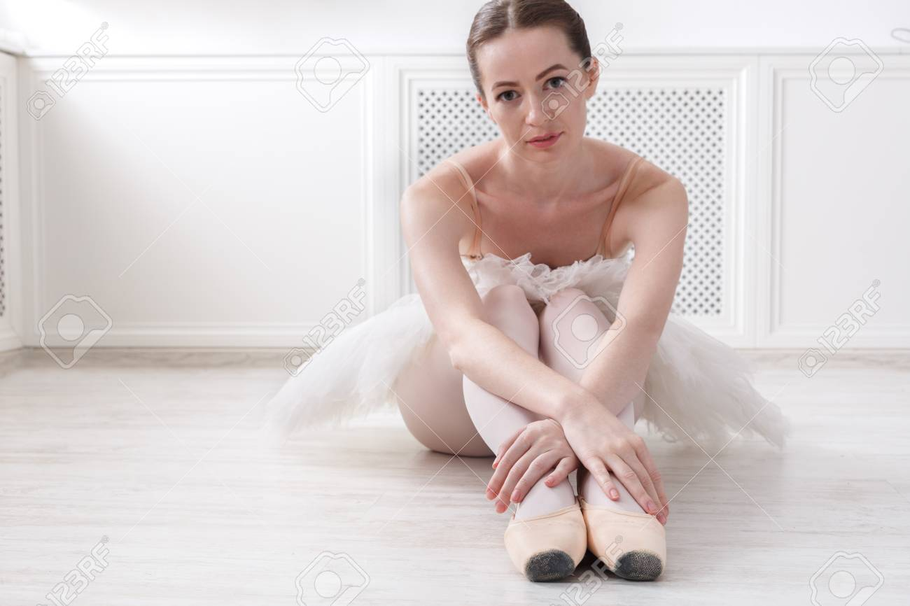 Beautiful graceful young ballerina in pointe shoes sit at white