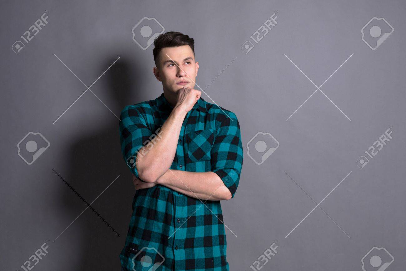 cfb1d4042c Ritratto Pensive del giovane in casuale alla priorità bassa grigia dello  studio. Ragazzo in camicia a scacchi
