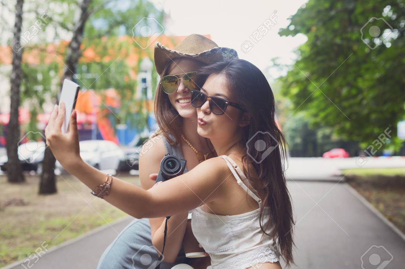 8fc3f15671 Stock Photo - Two girls friends take selfie with smartphone. Young female  tourists in boho chic fashion clothes