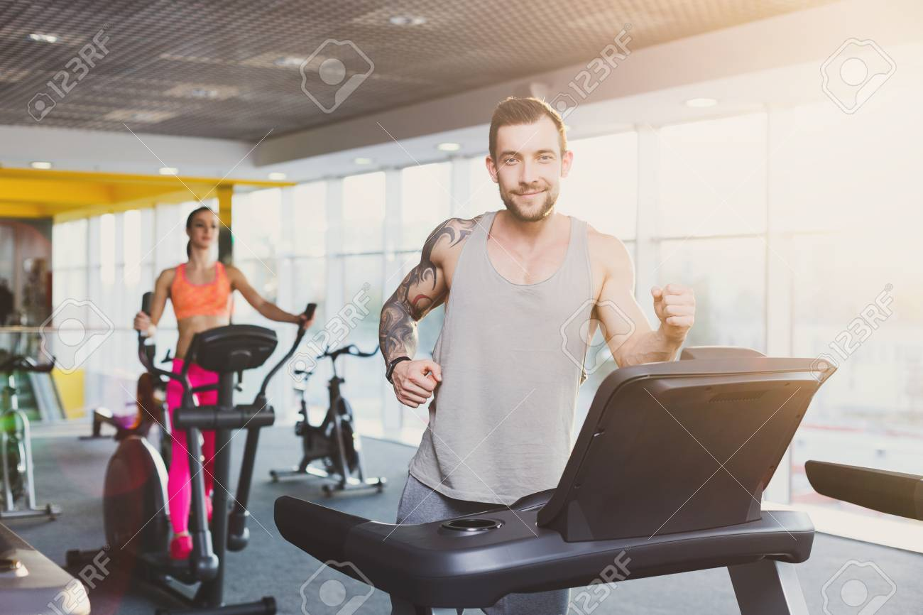 Ypoung Man Running On Treadmill In Fitness Club Cardio Workout