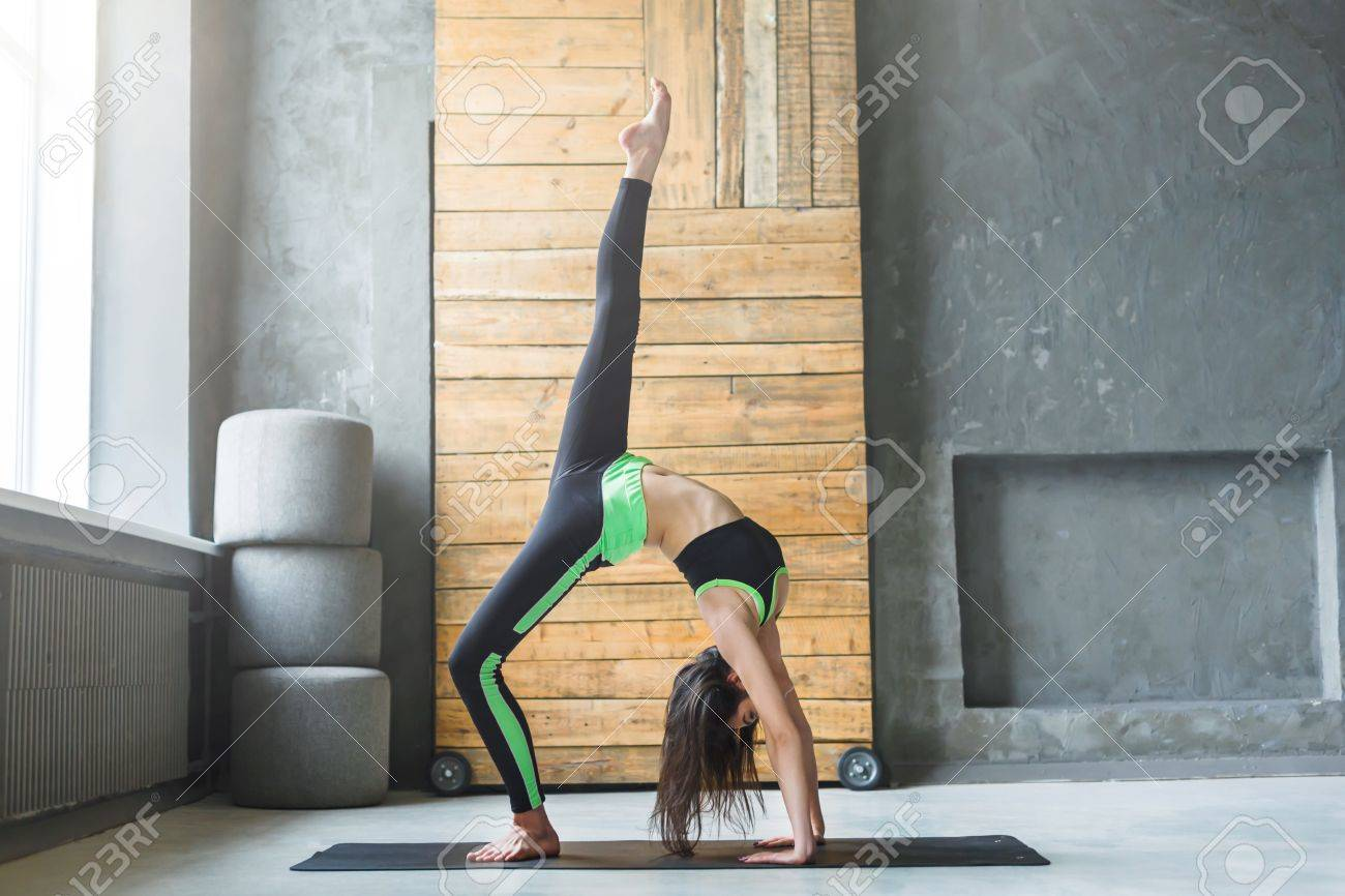 9c6db37fc34a8 Stock Photo - Young woman in yoga class making One-Legged wheel Pose.  Healthy lifestyle in fitness club. Stretching