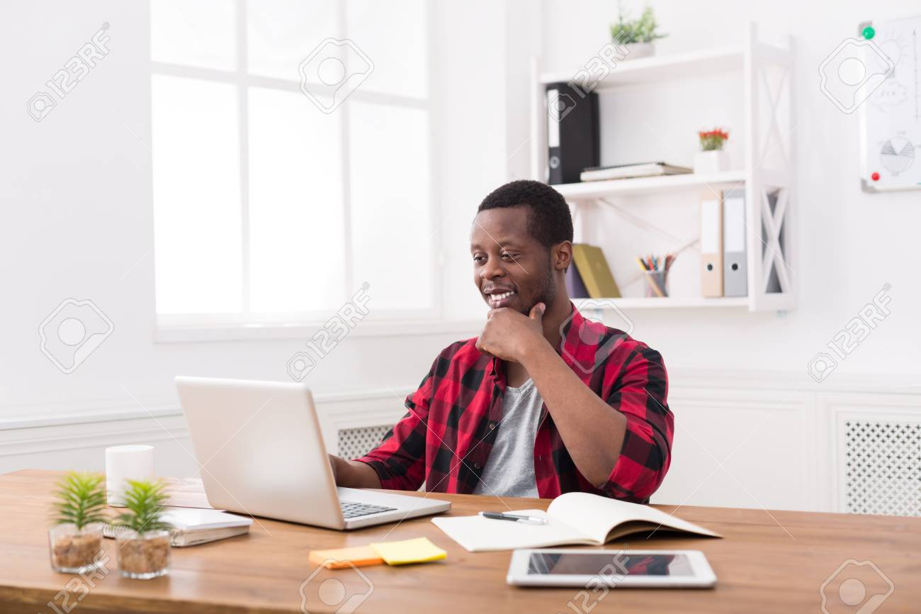 Heureux homme d affaires noir au bureau à l occasion travailler