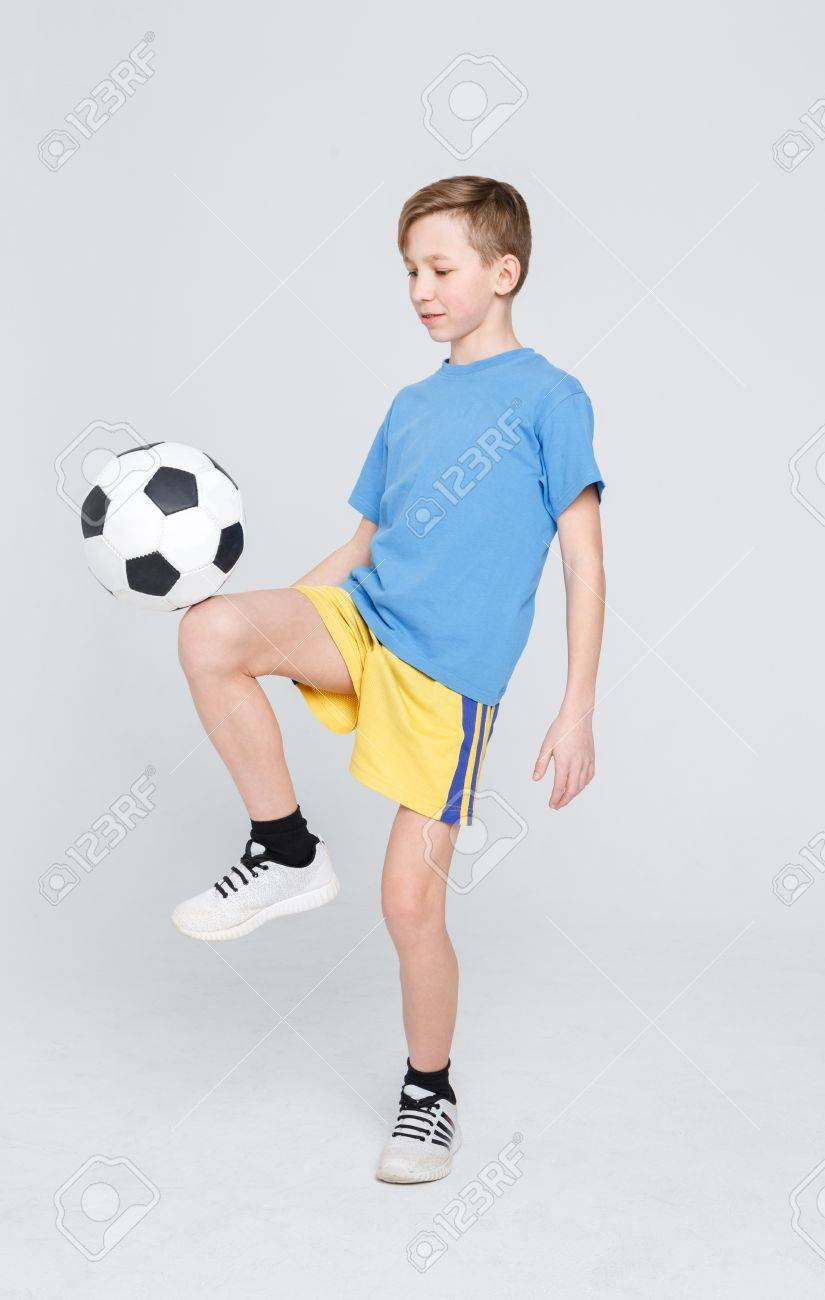 Ragazzo bello in abiti sportivi che fanno i trucchi con pallone da calcio  sopra il fondo bianco dello studio. Concetto di stile di vita attivo e  sportivo. 6098c864364