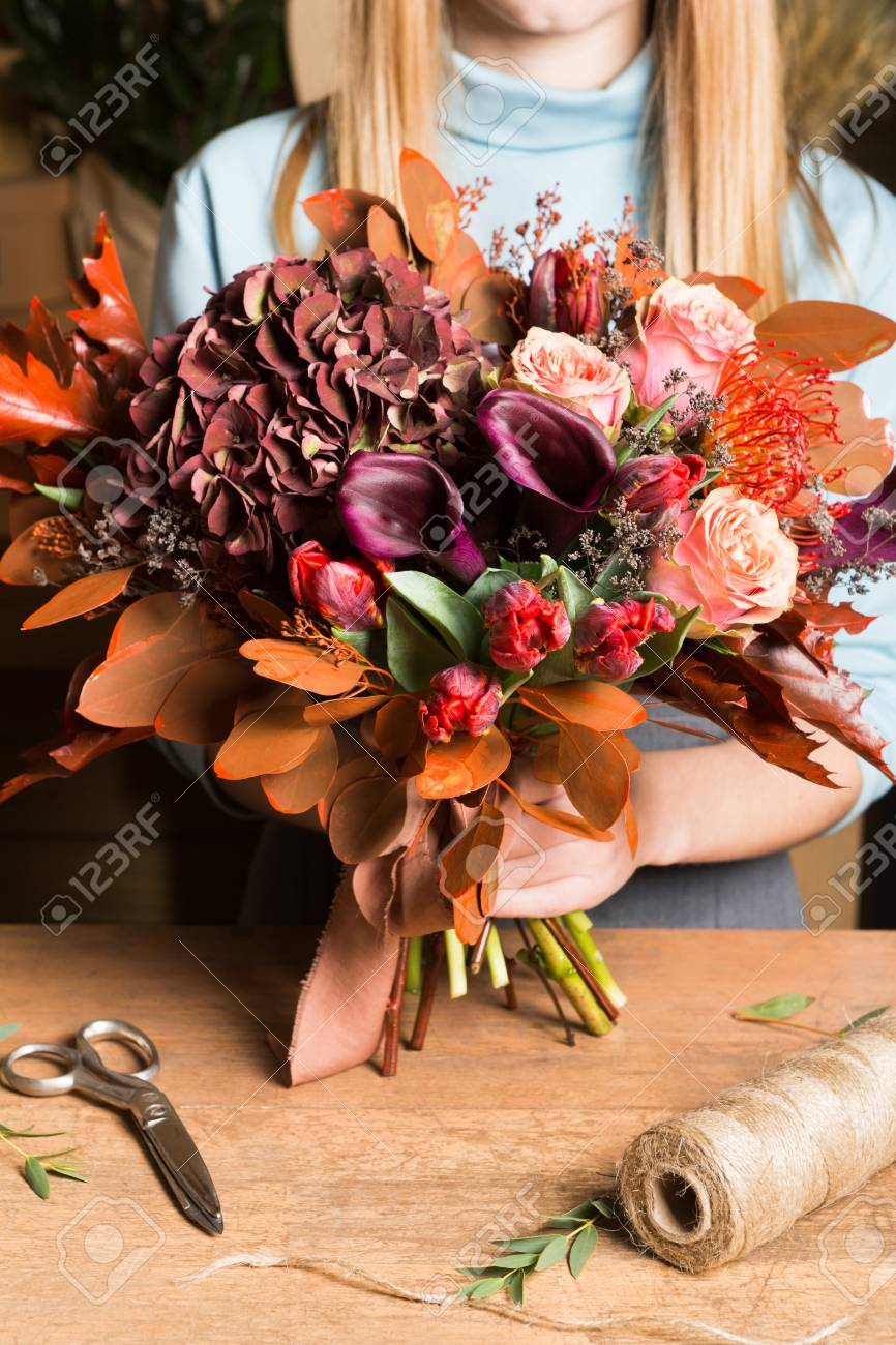 Female Florist Holding Colorful Fall Bouquet At Flower Shop Stock