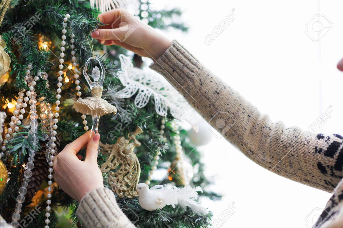 Female Hands Decorating Christmas Tree With Ballerina Figure
